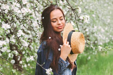 Portrait beautiful gentle hippie woman in stylish denim jacket relaxing on countryside garden with blossom trees. Young happy hipster girl posing with straw hat on green meadow. Floral spring nature 免版税图像