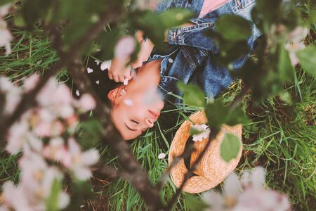 Top view young carefree hippie girl in stylish denim jacket laying on green grass on countryside garden with blossom tree. Happy beautiful hipster woman relaxing on calm, serene meadow. Girl outdoors