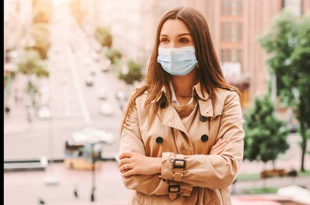 Young stylish hipster woman in protective face mask on city street. Beautiful happy girl in medical face mask keep arms crossed outdoors. Quarantine lifestyle, fashion. COVID-19 coronavirus, travel 免版税图像