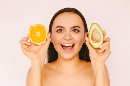 Portrait young funny girl posing with avocado and orange slice in hands and smile isolated on white background. Beautiful happy woman have fun with healthy fruits. Vitamin C, detox, cosmetology, diet