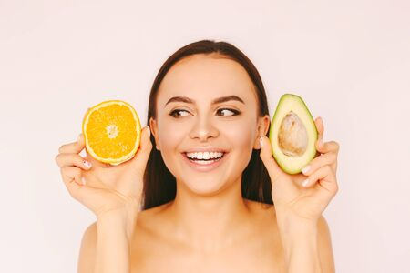 Portrait young cheerful girl posing with healthy fruits in hands isolated on white background. Beautiful happy funny woman have fun with avocado and orange slices. Beauty procedure, peeling, dieting