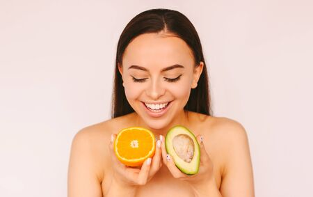 Portrait beautiful young woman have fun and smile with avocado and orange slices isolated on white background. Happy funny girl beauty model posing with healthy fruits. Skin care, dieting, cosmetology