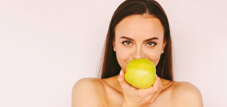 Portrait beautiful young girl posing with green apple in hand, smile isolated on white background. Attractive happy healthy woman eat apple fruit. Stomatology, dental treatment, oral care, dentistry