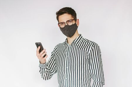Portrait confident young man professional entrepreneur in medical face mask and eyeglasses hold smart phone in hand isolated on white background. Businessman in protective face mask use mobile phone