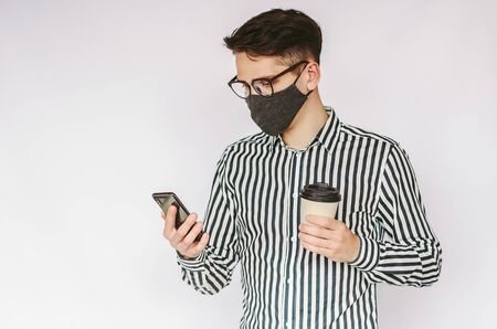 Portrait happy young man entrepreneur in medical face mask use mobile phone, drink coffee isolated on white background. Confident businessman in protective mask use smart phone for text messaging