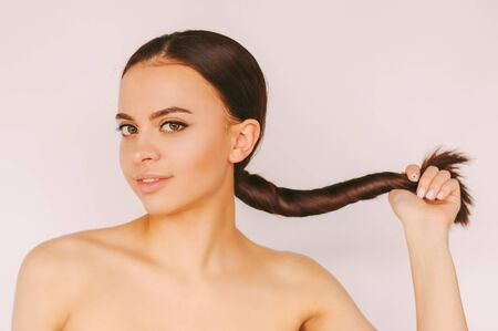 Portrait happy beautiful woman with perfect skin and long healthy brown hair isolated white background. Young attractive  girl beauty model with perfect pony tail hairstyle. Hair care, treatment Standard-Bild