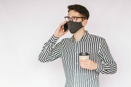 Young successful businessman in stylish protective face mask talk mobile phone and drink coffee isolated on white background. Happy male entrepreneur in medical face mask talk cell phone, coffee break