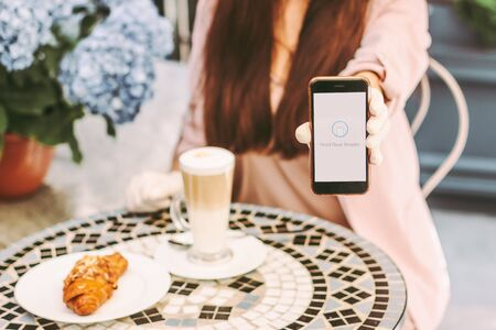 Closeup young stylish woman hold smart phone in hand to pay for coffee and croissant with contactlesss technology. Beautiful girl drink coffee at outdoor terrace of french cafe. NFC payment checkout Standard-Bild