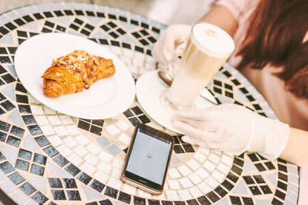 Closeup young woman in protective gloves drink coffee and croissant in vintage french cafe. Beautiful girl in medical glove in outdoor restaurant terrace. Smart phone with NFC mobile payment on screen Standard-Bild
