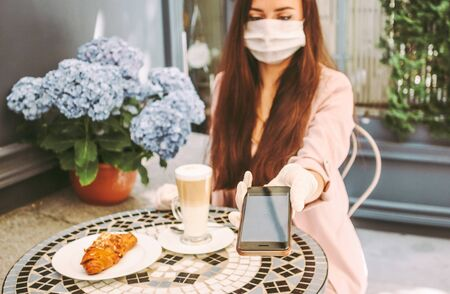 Portrait beautiful stylish woman in medical face mask use smart phone for contactless payment in outdoor french cafe. Young girl in protective face mask drink coffee, pay with NFC technology. COVID-19 Standard-Bild