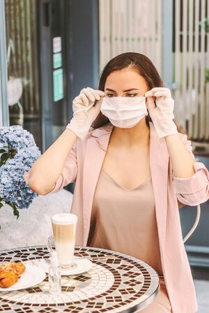 Portrait beautiful happy woman in protective gloves wearing medical face mask while drink coffee with croissant in outdoor french cafe. Young stylish girl in medical gloves put on protective face mask