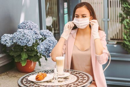 Portrait young happy girl in medical gloves put on protective face mask and drink coffee with croissant in outdoor french cafe. Beautiful stylish woman in protective gloves wearing medical face mask Standard-Bild