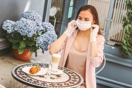 Portrait happy stylish woman in protective gloves drink coffee, wearing medical face mask in french outdoor cafe. Beautiful young girl in medical glove put on protective face mask. Personal protection