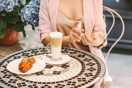 Beautiful woman apply hand sanitizer while drink coffee with croissant in french outdoor cafe. Young girl using antibacterial gel while sit on restaurant terrace. Personal safety, hygiene, protection Standard-Bild