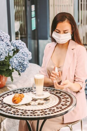 Portrait young beautiful girl in medical face mask apply hand sanitizer while drink coffee in outdoor french cafe. Stylish woman in protective face mask use antibacterial gel. Personal hygiene, safety