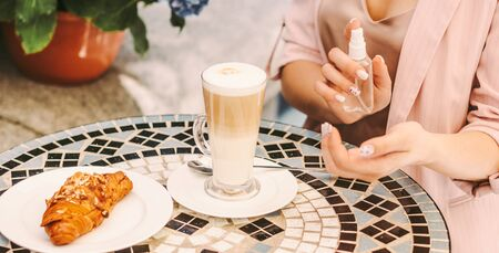 Closeup stylish girl use antibacterial antiseptic gel on hand, drink coffee in french outdoor cafe. Beautiful woman apply hand sanitizer on restaurant terrace. Personal protection, hygiene, safety