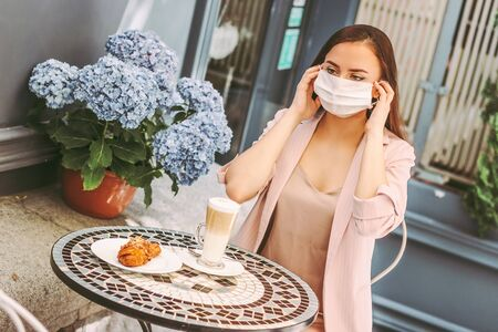 Portrait young beautiful woman wearing medical face mask while drink coffee on french cafe terrace. Happy stylish girl put on protective face mask in outdoor restaurant. Personal safety, COVID-19