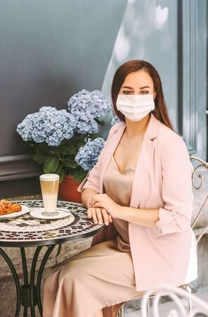 Portrait stylish beautiful business woman in protective face mask drink coffee in outdoor french cafe. Young girl drink coffee in medical face mask on restaurant terrace. COVID-19 quarantine lifestyle