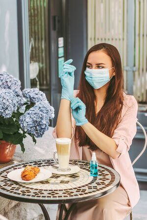 Portrait happy woman in medical face mask put on protective gloves and drink coffee on outdoor terrace in restaurant. Beautiful young girl in protective mask wear medical gloves sit in french cafe