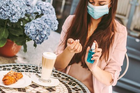 Portrait young woman in medical face mask apply hand sanitizer, drink coffee in restaurant. Beautiful girl in protective face mask use antibacterial gel. Personal safety, hygiene. COVID-19 protection