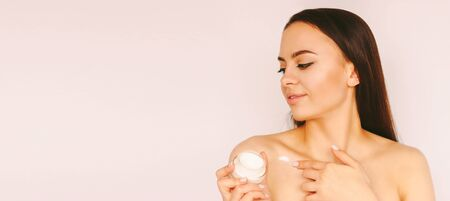 Portrait beautiful gentle girl posing with face cream jar in hand, smile isolated white background copy space. Young happy woman hold moisturizer lotion in hand. Beauty treatment, skin care, cosmetics