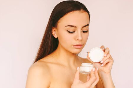 Portrait young attractive woman posing with face cream jar in hand isolated white background. Beautiful sensual girl hold moisturizing lotion jar. Natural female beauty, skin care cosmetics, treatment