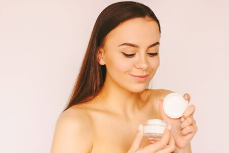 Portrait happy beautiful girl hold moisturizing lotion jar in hand and smile isolated white background. Young attractive woman posing with face cream jar. Natural beauty treatment, skin care cosmetics