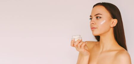 Banner young beautiful woman with perfect skin hold face cream jar in hand and look at copy space on white background. Happy attractive girl posing with moiturizing lotion jar. Beauty care cosmetics
