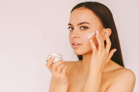Portrait beautiful young woman apply moisturizer face lotion isolated white background. Attractive sensual girl use face cream from jar for healthy smooth skin. Beauty treatment, body care cosmetics