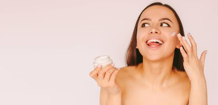 Banner young happy woman use face cream from jar for beauty treatment, skin care and perfect healthy smooth skin isolated on white background. Beautiful cheerful girl apply moisturizing lotion on face Standard-Bild