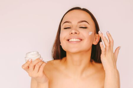Portrait cheerful attractive girl apply moisturizing lotion on face and have fun isolated white background. Beautiful happy woman use face cream for perfect smooth skin. Beauty, body care, hydration Standard-Bild