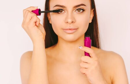 Portrait beautiful young woman apply mascara make up on face and smile isolated on white background. Happy attractive girl with perfect skin put mascara cosmetics with brush. Perfect beauty, make up
