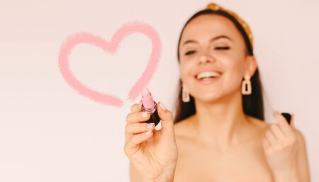 Portrait young cheerful stylish woman draw heart sign with lipstick and smile isolated white background. Beautiful happy girl have fun and apply lipgloss to make drawn love shape. Fashion, beauty