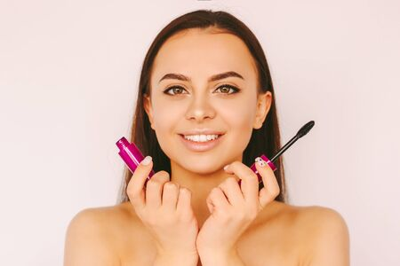 Portrait young beautiful woman posing with mascara brush in hands and smile isolated on white background. Happy attractive girl with perfect skin apply mascara facial cosmetics. Eyelash extension Standard-Bild