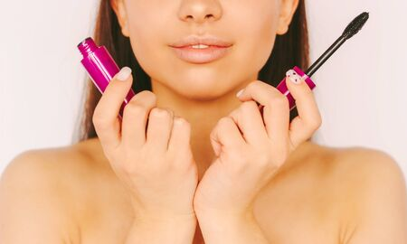 Closeup attractive young woman hold mascara brush in hands and smile isolated on white background. Beautiful happy girl apply mascara facial cosmetics. Beauty fashion model, luxury make up, grooming