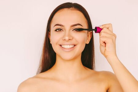 Portrait happy beautiful girl apply mascara cosmetics on long perfect eyelashes extension, smile isolated white background. Attractive young woman put mascara make up. Girl posing with mascara brush