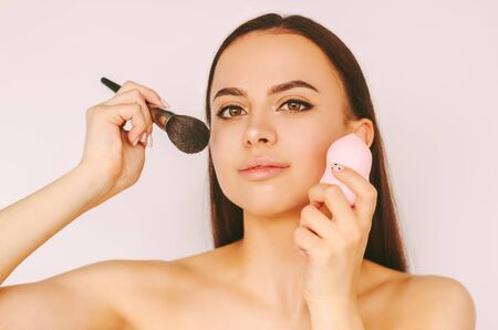 Portrait beautiful young woman apply foundation powder with beauty blender and brush isolated white background. Happy attractive girl put on make up on face. Female beauty model, skin care cosmetics