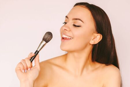 Portrait cheerful young attractive woman have fun and posing with make up brush in hand isolated white background. Beautiful happy girl apply foundation base on face and smile. Female make up artist