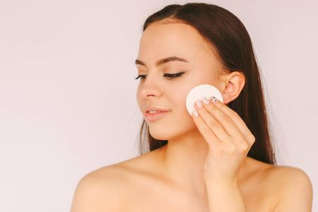 Portrait young sensual woman with perfect smooth skin remove make up on face with cotton pads isolated white background. Beautiful happy girl clean face from cosmetics. Cleansing lotion, skin care Standard-Bild
