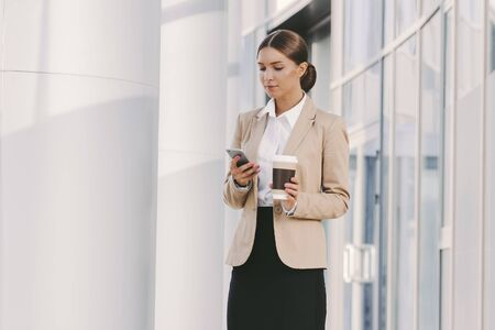 Portrait young beautiful business woman in stylish suit use smart phone and drink coffee outdoors. Attractive girl professional entrepreneur hold paper coffee cup and mobile phone in hand. Lunch break