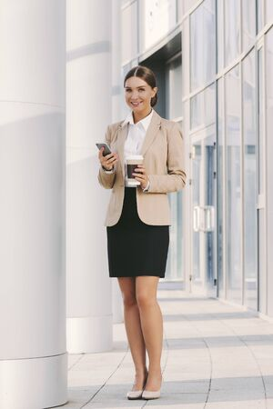 Portrait beautiful corporate girl professional entrepreneur drink coffee and use mobile phone outdoors. Attractive young business woman with smart phone and coffee cup in hands. Happy lady boss CEO