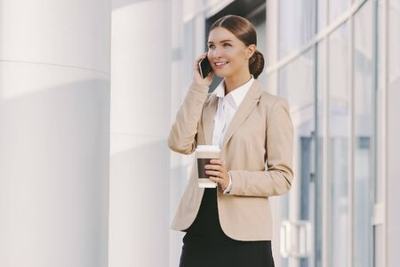 Portrait beautiful happy corporate girl boss talk mobile phone, drink takeaway coffee and smile outdoors. Young attractive professional business woman call smart phone. Girl lawyer on lunch break Standard-Bild