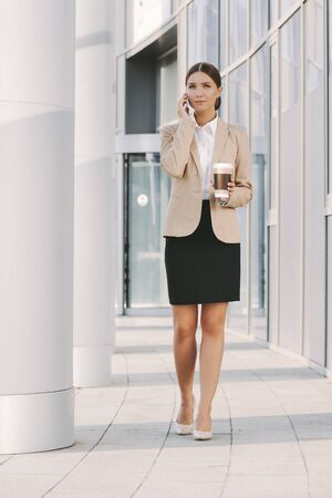 Beautiful professional business woman call mobile phone and drink coffee on lunch break near office building. Attractive happy girl lawyer talk cell phone and smile. Girl corporate lawyer lunch break