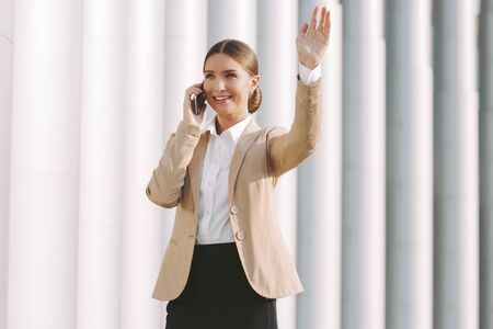 Portrait happy beautiful business woman in stylish suit talk cell phone and wave hand outdoors. Young attractive girl call mobile phone and wave hello to colleague. Corporate business communication