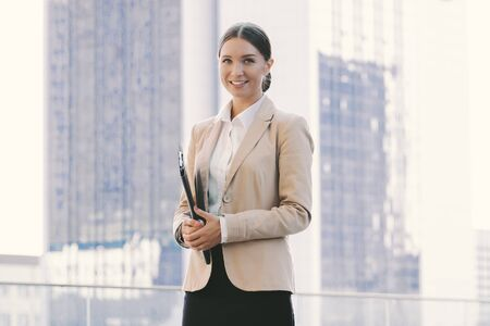Portrait beautiful successful business woman in suit hold documents folder and smile outdoors. Attractive young corporate girl with clipboard in hand on city street. Female entrepreneur, lawyer person