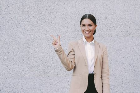 Portrait young beautiful millennial girl successful entrepreneur lawyer in suit gesture with index finger on copy space on gray background. Happy attractive business woman point up on copy space