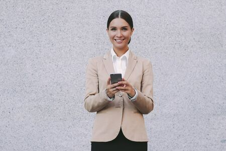 Portrait young attractive successful business woman in suit use smart phone and smile gray background. Beautiful happy female entrepreneur hold mobile phone in hands. Millennial girl corporate lawyer Standard-Bild