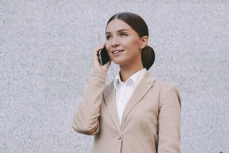 Portrait young beautiful successful business woman in suit talk mobile phone and smile on gray background. Attractive happy girl professional entrepreneur call on cell phone. Business communication