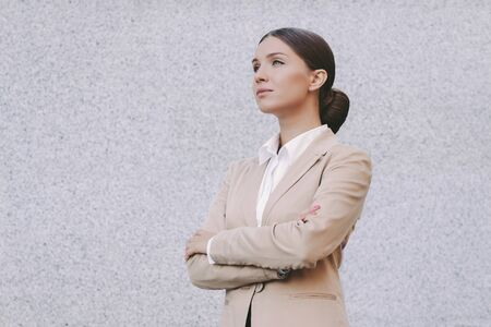 Portrait beautiful young business woman in suit keep arms crossed and look on copy space gray background. Attractive confident girl corporate lawyer with crossed arms. Successful female entrepreneur Standard-Bild