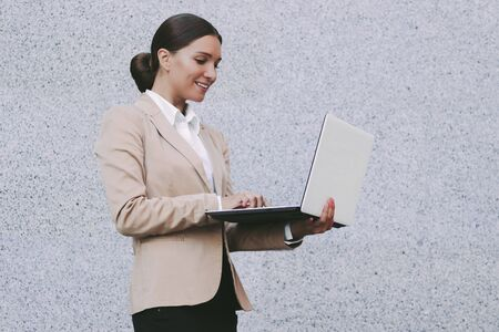 Portrait young attractive business woman in suit hold laptop in hand and smile on gray background. Beautiful happy female entrepreneur use computer. Corporate lawyer typing keyboard, surf internet